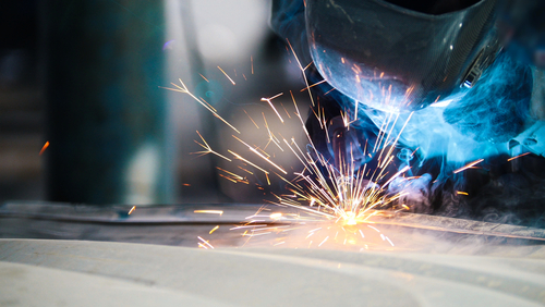 A welder uses a torch to complete a repair